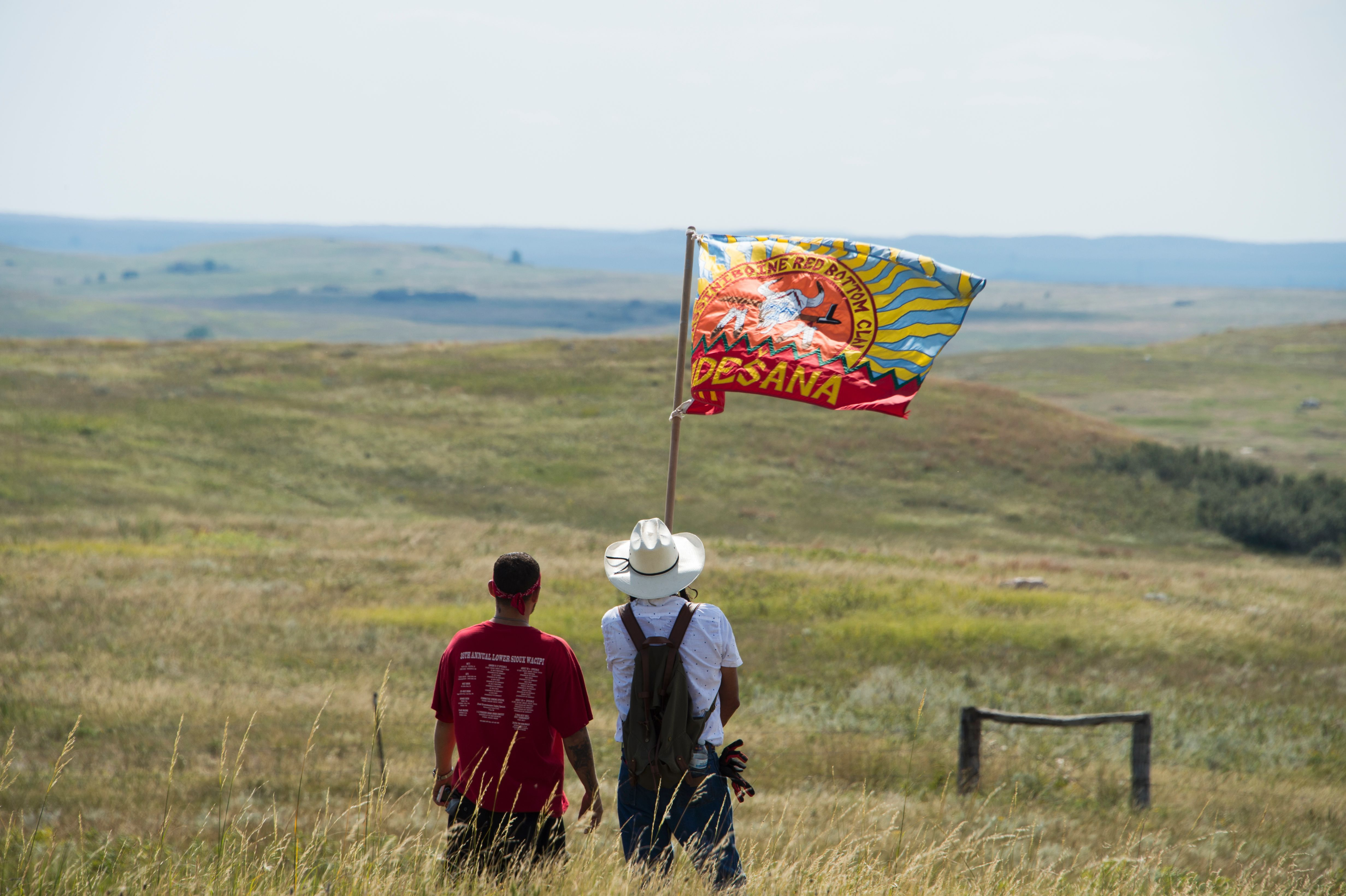 CORRECTION - Native American protestors wave a clan flag over land designated for the Dakota Access Pipeline (DAPL), after protestors confronted contractors and private security guards working on the oil pipeline project, forcing them to retreat,  September 3, 2016, near Cannon Ball, North Dakota.   Hundreds of Native American protestors and their supporters, who fear the Dakota Access Pipeline will polluted their water, forced construction workers and security forces to retreat and work to stop. / AFP / Robyn BECK / The erroneous mention[s] appearing in the metadata of this photo by Robyn BECK has been modified in AFP systems in the following manner: [Native American protestors wave a clan flag over land designated for the Dakota Access Pipeline (DAPL), after protestors confronted contractors and private security guards working on the oil pipeline project, forcing them to retreat,  September 3, 2016, near Cannon Ball, North Dakota.] instead of [A protestor is treated after being pepper sprayed by private security contractors on land being graded for the Dakota Access Pipeline (DAPL) oil pipeline, near Cannon Ball, North Dakota, September 3, 2016.]. Please immediately remove the erroneous mention[s] from all your online services and delete it (them) from your servers. If you have been authorized by AFP to distribute it (them) to third parties, please ensure that the same actions are carried out by them. Failure to promptly comply with these instructions will entail liability on your part for any continued or post notification usage. Therefore we thank you very much for all your attention and prompt action. We are sorry for the inconvenience this notification may cause and remain at your disposal for any further information you may require.        (Photo credit should read ROBYN BECK/AFP/Getty Images)